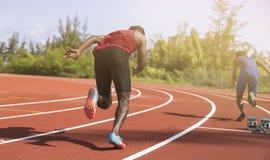 Atletische jonge mens die op rasspoor lopen met bokeh groene achtergrond Stock Foto