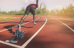 Atletische jonge mens die op rasspoor lopen met bokeh groene achtergrond Royalty-vrije Stock Afbeelding