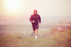 Atletische jonge mens die tijdens de herfst, de winterochtend lopen Royalty-vrije Stock Afbeelding