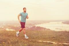 Atletische jonge mens die tijdens de herfst, de winterochtend lopen Royalty-vrije Stock Foto's
