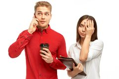 Atletische jonge mens met blond haar die op de telefoon met Kop van koffie in zijn handen spreken stock foto