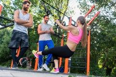 Atletische jonge vrouw die bicep krullen met een opschortingstrainer doen stock fotografie