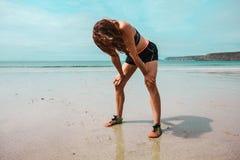 Atletische jonge vrouw die na het lopen op strand rusten stock foto