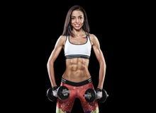 Atletische jonge vrouw die training met gewichten op donkere backgrou doen Stock Afbeelding