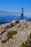 Atletische jonge vrouw die zich op de rotsachtige bovenkant van de berg a bevindt royalty-vrije stock afbeelding