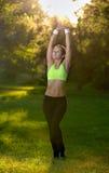 Atletische jonge vrouw in sportenkleding die fitness rek doen stock foto