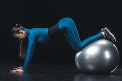 Atletische jonge vrouw in sportkleding die met geschiktheidsbal uitoefenen Royalty-vrije Stock Afbeeldingen