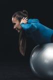 Atletische jonge vrouw in sportkleding die met geschiktheidsbal uitoefenen Stock Afbeelding