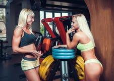 Atletische jonge vrouwen die tijdens oefening rusten Stock Fotografie
