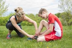Atletische jongen die haar Pijnlijke Verwonde enkel houden stock foto