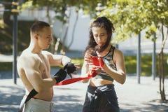 Atletische Kaukasische man en vrouwen verpakkende handen met verbanden voor training in de zomerpark Stock Foto