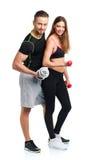 Atletische man en vrouw met domoren op het wit Royalty-vrije Stock Foto's