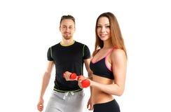 Atletische man en vrouw met domoren op het wit Stock Foto