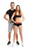 Atletische man en vrouw met domoren op het wit Stock Afbeeldingen