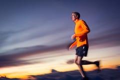 Atletische mens die bij zonsondergang lopen Stock Foto's