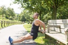 Atletische mens die en op bank opleiden uitoefenen, openlucht stock foto