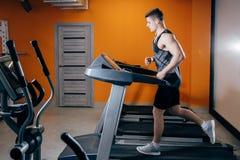 Atletische mens die op de tredmolen loopt stock fotografie