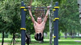 Atletische mens die opheffende benen op rekstok in Stadspark doen De atletische mens oefent abdominals op rekstok uit stock videobeelden