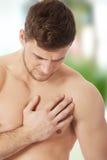 Atletische mens die pijn in zijn borst voelen stock afbeeldingen
