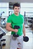 Atletische mens in een groene t-shirt met domoren de handen van spo Royalty-vrije Stock Foto