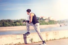 Atletische mens met het geschikte spierlichaam rusten na jogging dichtbij r stock afbeelding