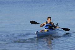 Atletische mensenruggen in baai in kajak stock afbeeldingen