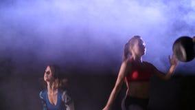 Atletische sexy vrouwen, die geschiktheidsoefeningen met wegingen doen, bij nacht, in lichte rook, mist, gezien een stobascope stock video