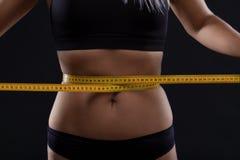 Atletische slanke vrouw die haar taille meten door maatregelenband na een dieet over zwarte achtergrond stock fotografie