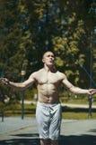 Atletische spiermens die met een kabel, training in openlucht bij zonnige dag springen Stock Afbeeldingen