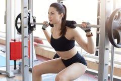 Atletische sterke jonge dame die terug hurkzit doen, doorbrengend haar vrije tijd in gymnastiek, die haar lichaam in perfecte vor stock fotografie
