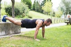 Atletische sterke mens die opdrukoefeningen doen, openlucht royalty-vrije stock foto