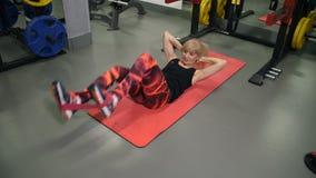 Atletische vrouw bij de gymnastiek die een oefening op de pers doen, die op mat4k Langzame Mo liggen stock video