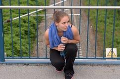 Atletische Vrouw die bij de Brug met Water hurken stock foto's