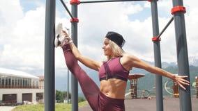Atletische vrouw die enige been gespleten hurkende oefening met hoge gebouwen van het parkmateriaal de in openlucht op achtergron stock video