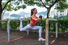 Atletische vrouw die enige been gespleten hurkende oefening met hoge gebouwen van het parkmateriaal de in openlucht op achtergron Royalty-vrije Stock Afbeeldingen