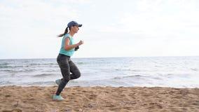 Atletische vrouw die langs het strand lopen Video bij verschillende snel, normaal en langzame snelheden - stock footage