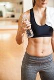 Atletische vrouw die met abs wat water drinken royalty-vrije stock fotografie
