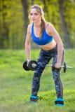 Atletische vrouw die oefening voor wapens doen Foto van het spiergeschiktheid model uitwerken met domoren Sterkte en motivatie royalty-vrije stock foto