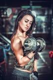 Atletische vrouw die omhoog muscules met domoren pompen Royalty-vrije Stock Afbeelding