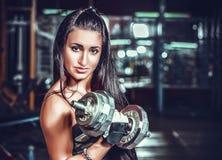 Atletische vrouw die omhoog muscules met domoren pompen Stock Afbeelding