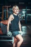 Atletische vrouw die omhoog muscules met domoren pompen Stock Foto's