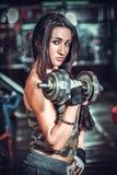 Atletische vrouw die omhoog muscules met domoren pompen Stock Fotografie