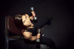 Atletische vrouw die omhoog muscules met domoren in pompen Stock Afbeelding