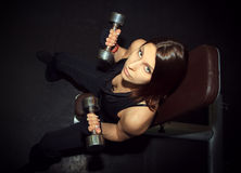 Atletische vrouw die omhoog muscules met domoren in pompen Royalty-vrije Stock Afbeelding