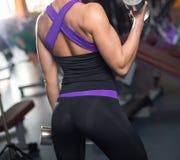 Atletische vrouw die omhoog spieren met domoren pompen Stock Afbeeldingen