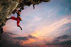 Atletische Vrouw die op overhangende klippenrots beklimmen met de achtergrond van de zonsonderganghemel royalty-vrije stock afbeeldingen