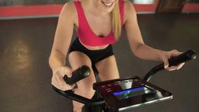 Atletische vrouw die stationaire fiets berijden en elektronisch paneel, sport bekijken stock footage
