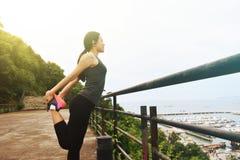 Atletische vrouw die vóór haar ochtendtraining opwarmen Stock Foto's