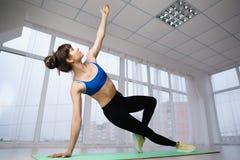 Atletische vrouw die zijplank doen bij yogastudio royalty-vrije stock afbeelding