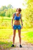 Atletische vrouw in sportkleding die in een park in de ochtend uitoefenen Royalty-vrije Stock Afbeeldingen